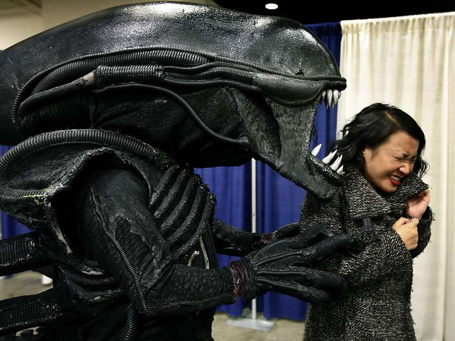 "Kristy Huynh recoils from Matthew O'Connor, who is dressed as the ""Alien,"" at the WonderCon comic book convention in San Francisco on Saturday. Photo: Paul Chinn, The Chronicle"