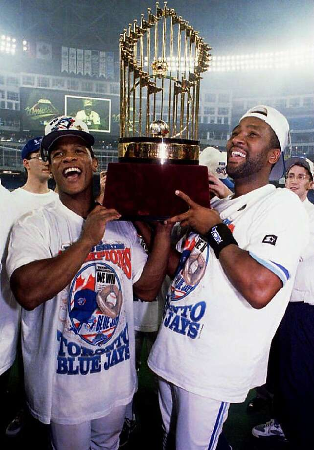 TORONTO, CANADA - OCTOBER 23:  Toronto Blue Jays Rickey Henderson (L) and Joe Carter lift the World Series trophy for Blue Jays fans late 23 October 1993, in Ontario, Canada, after the Blue Jays won game six 8-6 over the Philadelphia Phillies and clinched the World Series. This is the second straight World Series victory for the Jays.  (Photo credit should read CARLO ALLEGRI/AFP/Getty Images) Photo: Carlo Allegri, AFP/Getty Images