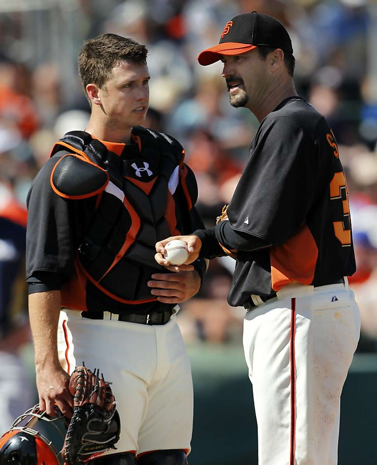 Buster Posey meets on the mound with reliever Jeff Suppan in the Giants' spring training game against the Milwaukee Brewers at Scottsdale Stadium in Scottsdale, Ariz., on Monday.