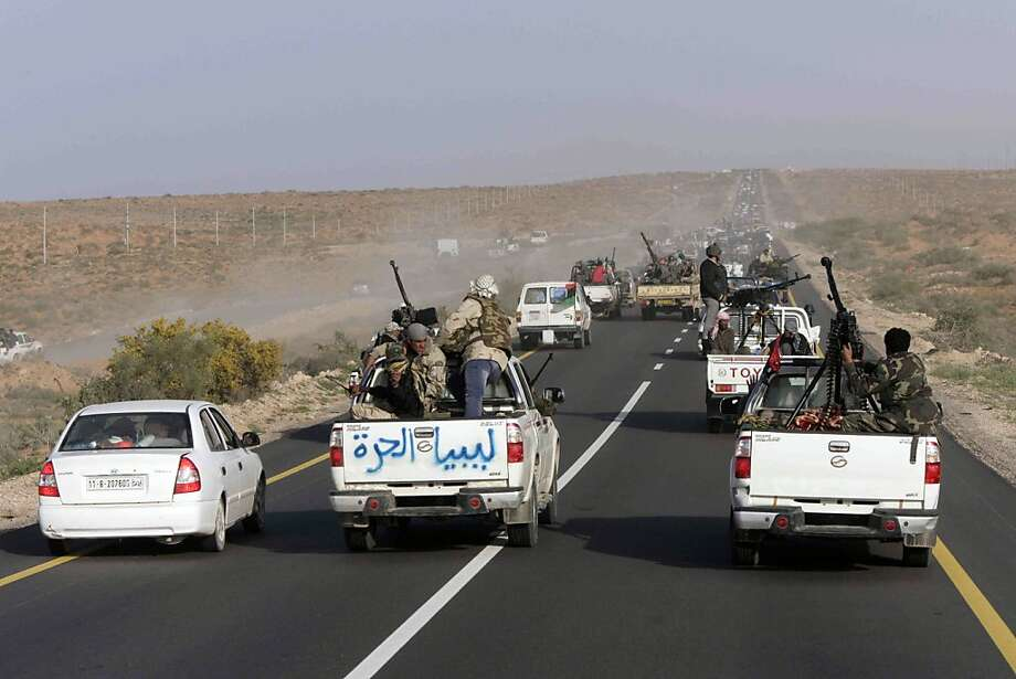 "Libyan rebels vehicles pack the road between between Ras Lanouf and Sirte in eastern Libya, Monday, March 28, 2011.  Rebel forces bore down Monday on Moammar Gadhafi's hometown of Sirte, a key government stronghold where a brigade headed by one of the Libyan leader's sons was digging in to defend the city and setting the stage for a bloody and possibly decisive battle. The writing on the truck reads ""Free Libya"" in Arabic. Photo: Str, AP"