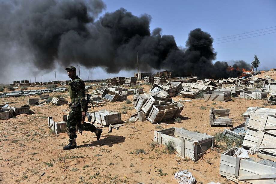 Libyan rebels burn an electricity equipment storage facility as they advance from the village of Harawa towards Moamer Kadhafi's hometown of Sirte on March 28, 2011 as NATO finally agreed to take over full command of military operations to enforce a no-fly zone in Libya from a US-led coalition. Photo: Aris Messinis, AFP/Getty Images
