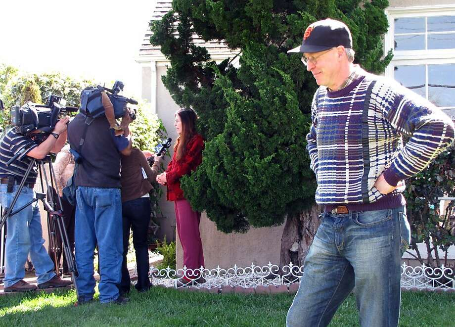 Wally Oliver stands in front of his Redwood City house as his wife Cherie Oliver, in the background, answers media questions after Department of Fish and Game authorities shot and killed a mountain lion in their backyard Tuesday morning. It was the firsttime the couple had seen a wild animal other than squirrels or the occasional raccoon in the residential neighborhood. Photo: Jill Tucker, The Chronicle