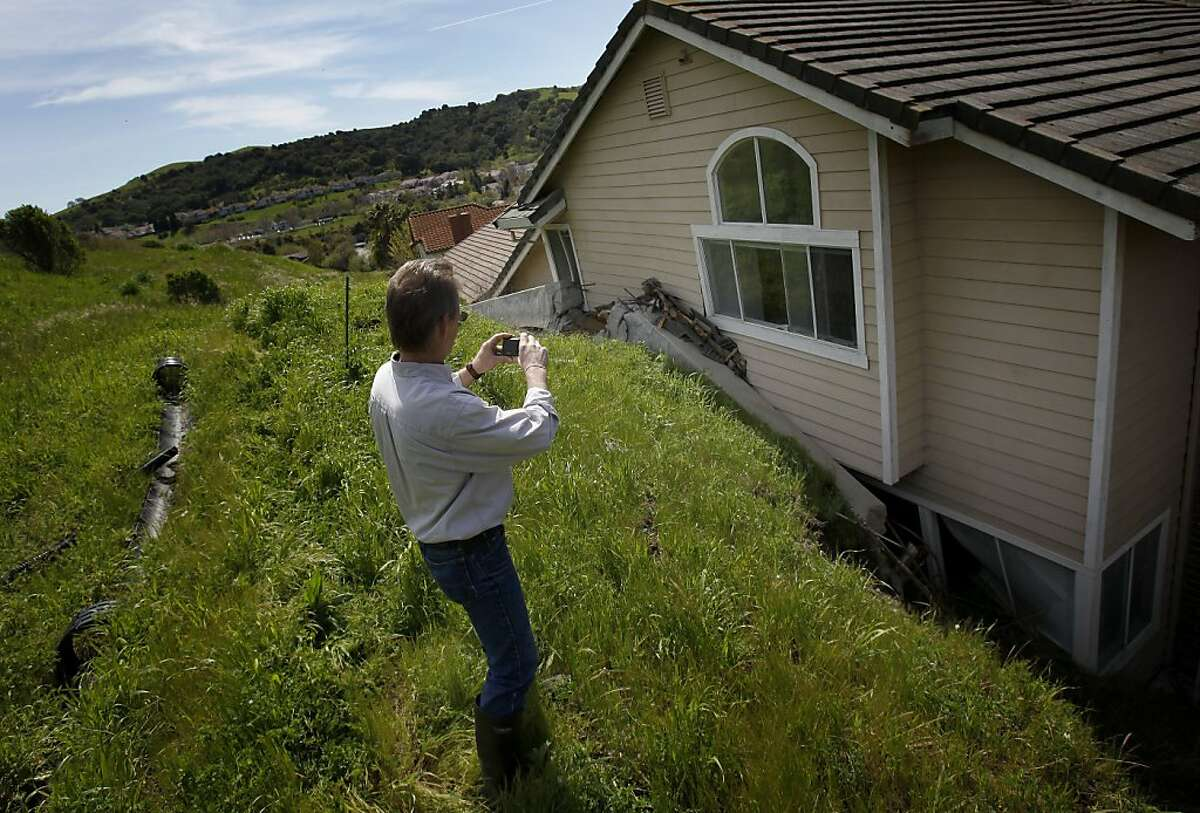 Ernie Visconti of the Hercules building department takes pictures of a home whose concrete retaining wall was literally smashed against the back of the house. A landslide in an upscale Hercules neighborhood has red tagged four homes on Carson Street.