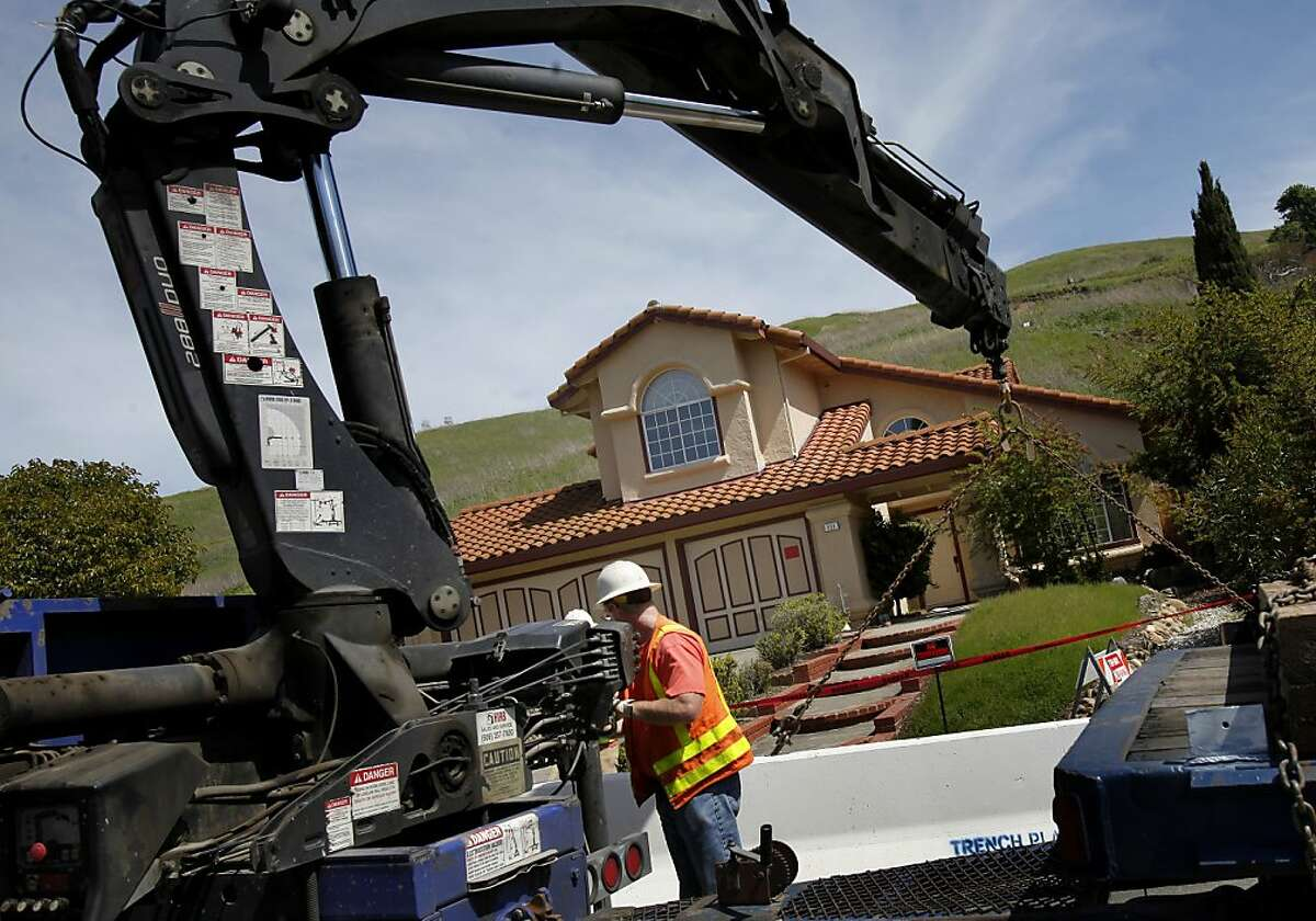 Workers place large cement blocks in front of a red tagged home. A landslide in an upscale Hercules neighborhood has red tagged four homes on Carson Street.