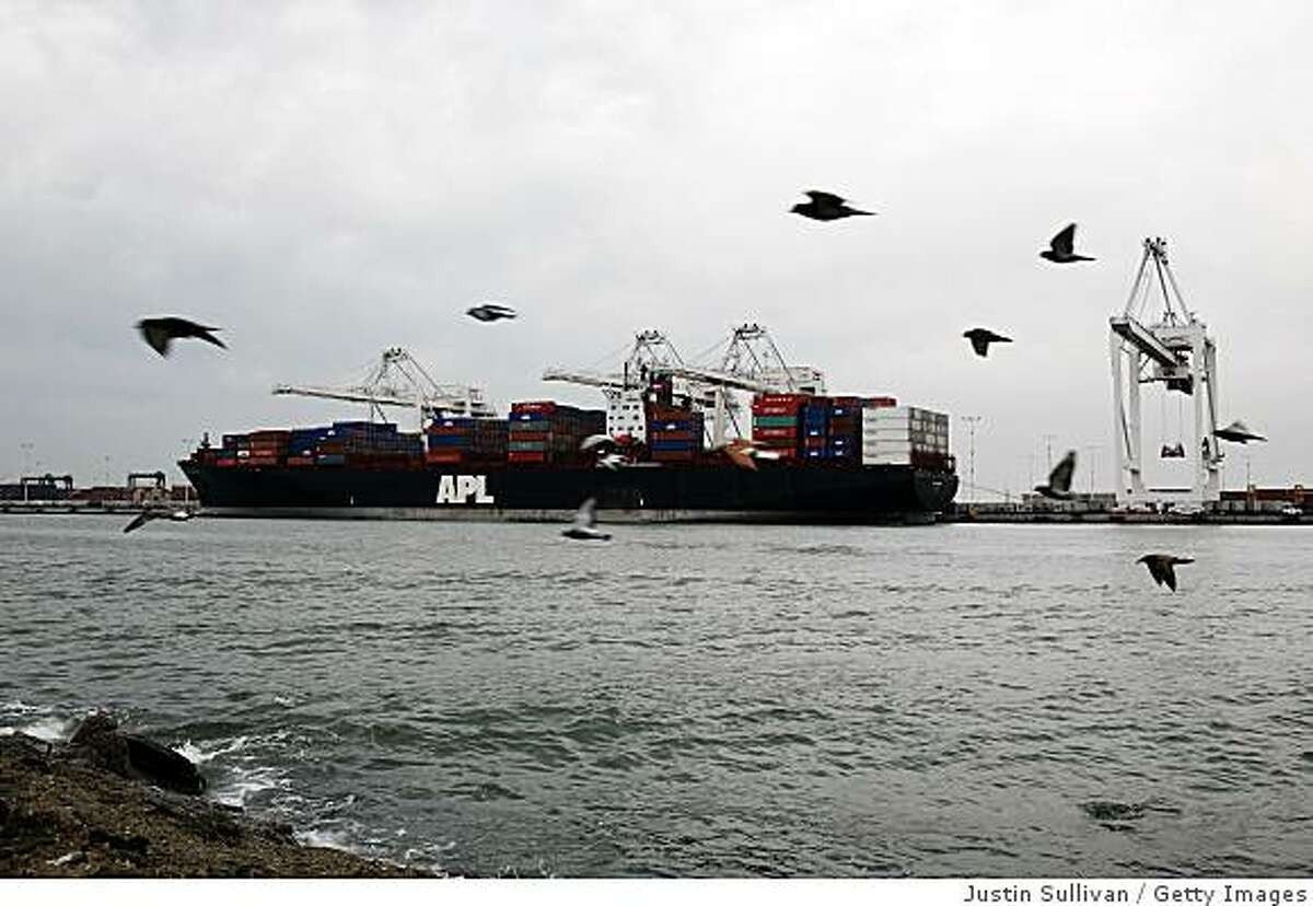 OAKLAND, CA - OCTOBER 30: Birds fly by a container ship that is docked at the Port of Oakland October 30, 2008 in Oakland, California. The GDP fell 0.3% as consumer spending hit a 28-year low. (Photo by Justin Sullivan/Getty Images)