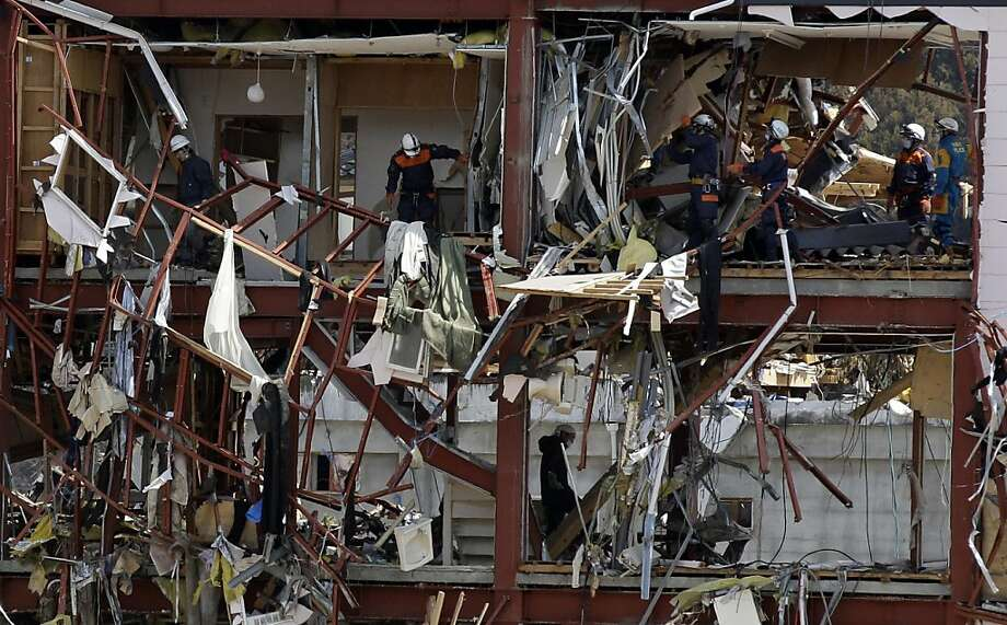 Japanese policemen search for victims in the debris at the March 11 earthquake and tsunami-destroyed town of Rikuzentakata, Iwate Prefecture, northern Japan, Friday, April 1, 2011. Photo: Lee Jin-man, AP