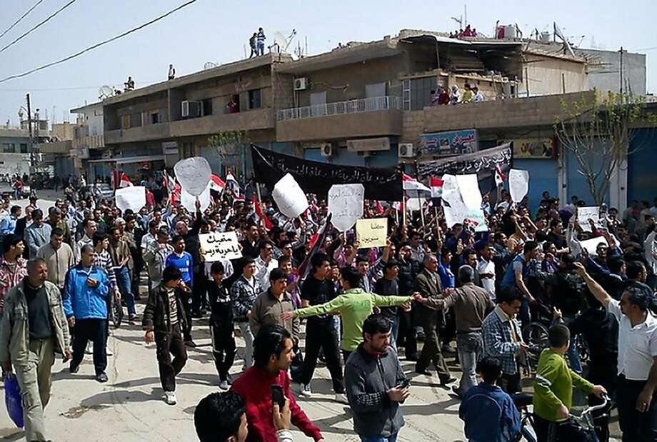 """AFP IS USING PICTURES FROM ALTERNATIVE SOURCES AS IT WAS NOT AUTHORISED TO COVER THIS EVENT, THEREFORE IT IS NOT RESPONSIBLE FOR ANY DIGITAL ALTERATIONS TO THE PICTURE'S EDITORIAL CONTENT, DATE AND LOCATION WHICH CANNOT BE INDEPENDENTLY VERIFIED Syrian anti-government protesters, some holding signs reading """"We only love freedom"""", march in the northeastern town of Qamishli on April 1, 2011 as hundreds of Syrians emerged from Friday prayers to protest in the first rallies since President Bashar al-Assad dashed hopes for greater freedoms. Photo: -, AFP/Getty Images"""