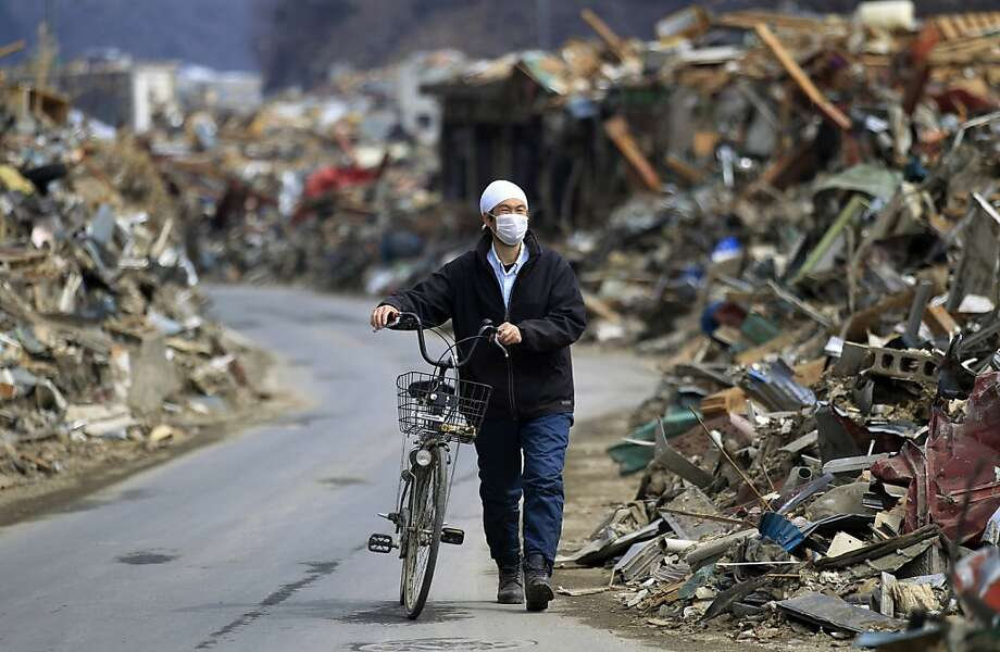 A man pushes his bicycle through the rubble at the earthquake and tsunami devastated area in Onagawa, Miyagi Prefecture, northern Japan, Thursday, March 31, 2011. Photo: Eugene Hoshiko, AP