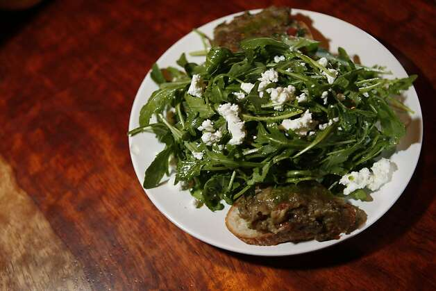 An arugula salad with goat cheese and eggplant caviar waits to be served in the restaurant Radio Africa and Kitchen at The Corner in San Francisco Calif, on Friday, Feb. 25, 2011. Photo: Alex Washburn, The Chronicle