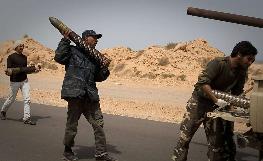 Libyan rebels load ammunition on the frontline outside of Bin Jawaad, 150 km east of Sirte, central Libya, Tuesday, March 29, 2011. Libyan government tanks and rockets blunted a rebel assault on Moammar Gadhafi's hometown of Sirte on Tuesday and drove back the ragtag army of irregulars, even as world leaders prepared to debate the country future in London.  (AP Photo/Anja Niedringhaus) Photo: Anja Niedringhaus, AP