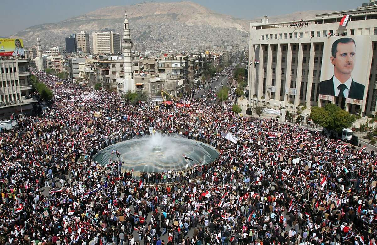 Thousands of Syrians rally to show their support for President Bashar al-Assad (portrait), who is facing unprecedented domestic pressure amid a wave of dissent, in Damascus on March 29, 2011.