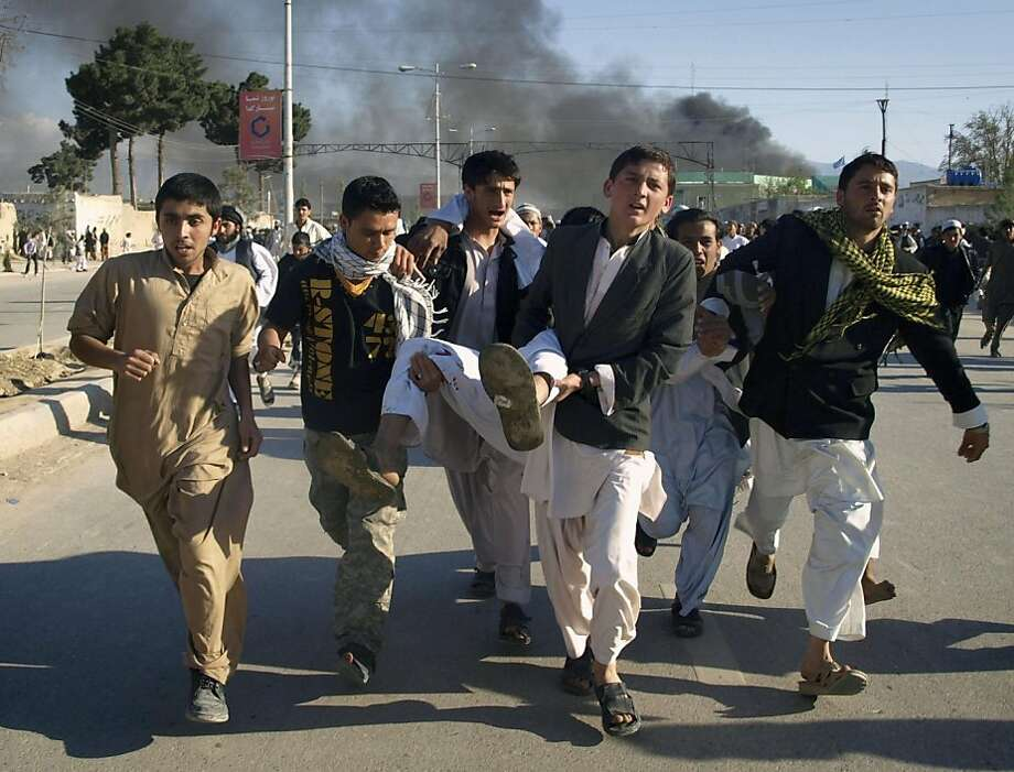 Afghans carrying a man, who got wounded following an attack on UN's office during a demonstration to condemn the burning of a copy of the Muslim holy book by a Florida pastor, in Mazar-i- Sharif north of Kabul, Afghanistan on Friday, April. 1, 2011. An Afghan official says seven people have been killed at a U.N. office in the northern city of Mazar-i-Sharif when a Quran burning protest turned violent. Photo: Mustafa Najafizada, AP