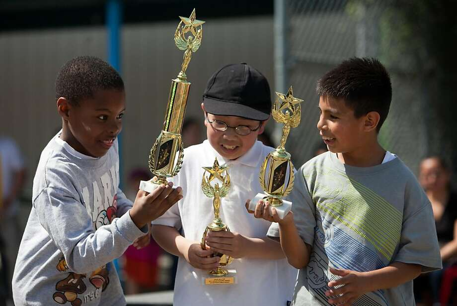 Rashad Cohen, 8 David Nguyen, 9 and Juan Villavicencio, 8 all in 3rd grade check out their trophies they received after meeting all their reading goals at the Lezear Elementary School, April 1, 2011 in Oakland, Calif.  Photograph by David Paul Morris/Special to the Chronicle Photo: David Paul Morris, Special To The Chronicle