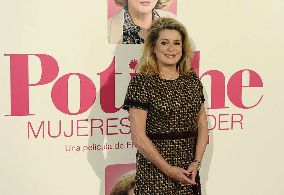 """French actress Catherine Deneuve poses during a photocall for the presentation of French director Francois Ozon's movie """"Potiche"""" in Madrid on March 18, 2011.  Based on a play of the same name -- which translates with difficulty as """"trophy wife"""" -- the comedy relates the unlikely transformation of bourgeois housewife Suzanne Pujol (Deneuve) into company executive and her complex relationship with a tough-as-nails union leader played by Depardieu. Photo: Pierre-philippe Marcou, AFP/Getty Images"""