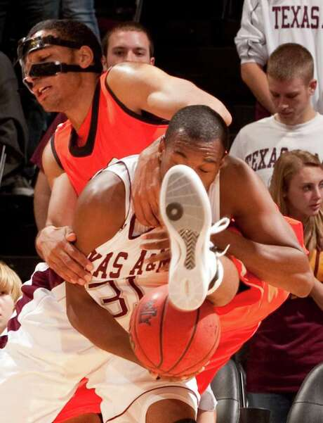 DAVE EINSEL: ASSOCIATED PRESS SHOE IN: Texas A&M's Elston Turner, front, grabs a rebound even though Michael Holyfield puts his best foot forward. Photo: Dave Einsel / FR43584 AP