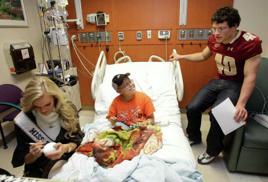 MELISSA PHILLIP: CHRONICLE GOOD CHEERLEADERS: Lombardi winner Luke Kuechly, right, and Miss Texas Brittany Booker visit 11-year-old Cesar Guerra of Magnolia on Wednesday at MD Anderson Cancer Center. Photo: Melissa Phillip / © 2011 Houston Chronicle