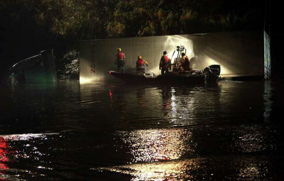 A rescue and recovery crew works to secure a semi after the truck broke through a guardrail and landed in the Duwamish River on northbound State Route 99 on Wednesday, December 7, 2011. The truck floated about 100 yards before it hit bottom in the river. The truck was reportely carrying a load of fish. Photo: JOSHUA TRUJILLO / SEATTLEPI.COM