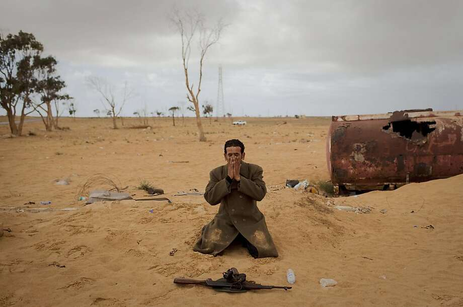 """A Libyan rebel prays next to his gun on the frontline of the outskirts of the city of Ajdabiya, south of Benghazi, eastern Libya, Monday, March 21, 2011. The international military intervention in Libya is likely to last """"a while,"""" a top French official said Monday, echoing Moammar Gadhafi's warning of a long war ahead as rebels, energized by the strikes on their opponents, said they were fighting to reclaim a city under siege from the Libyan leader's forces. Photo: Anja Niedringhaus, AP"""