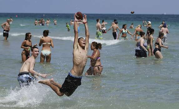 Kevich Vargas. left, watches as his friend, Arcain Meza, catches a football Thursday, March 17, 2011 on the beach in Fort Lauderdale, Fla. during spring break. Spring Break 2011 marks the 50th anniversary of Spring Break as a major cultural event. Photo: AP