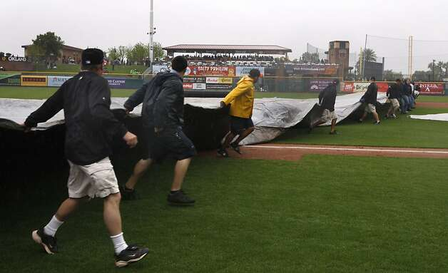 Groundskeepers cover the infield after umpires declared a rain delay in the Giants spring training baseball game against the Colorado Rockies at Scottsdale Stadium in Scottsdale, Ariz. on Monday, March 21, 2011. The game was officially cancelled in the 3rd inning. Photo: Paul Chinn, The Chronicle
