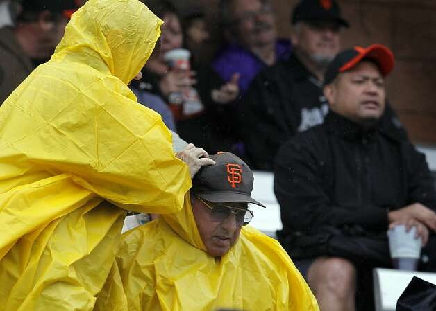 A man gets help with his poncho during a rain delay in the Giants spring training baseball game against the Colorado Rockies at Scottsdale Stadium in Scottsdale, Ariz. on Monday, March 21, 2011. The game was officially cancelled in the 3rd inning. Photo: Paul Chinn, The Chronicle