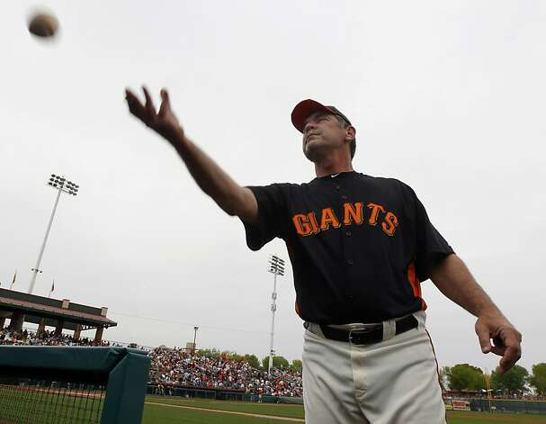 Manager Bruce Bochy returns a ball to a fan after autographing it before the Oakland A's 6-4 win over the San Francisco Giants in a spring training game at Scottsdale Stadium in Scottsdale, Ariz., on Sunday. Photo: Paul Chinn, The Chronicle
