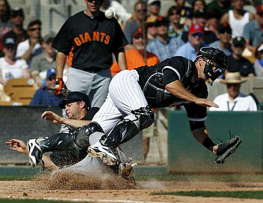 Brandon Belt scores with a hard slide on White Sox catcher Donny Lucy in  the 7th inning of the Giants 5-3 win over the Chicago White Sox in a spring training baseball game at Camelback Ranch stadium in Glendale, Ariz. on Wednesday, March 16, 2011. Photo: Paul Chinn, The Chronicle
