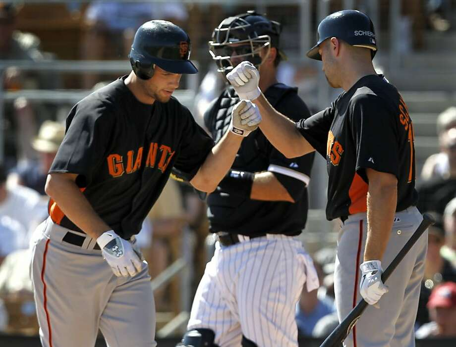 Brandon Belt (left) is congratulated by Nate Schierholtz after belting a homer in the 6th inning of the Giants 5-3 win over the Chicago White Sox in a spring training baseball game at Camelback Ranch stadium in Glendale, Ariz. on Wednesday, March 16, 2011. Photo: Paul Chinn, The Chronicle