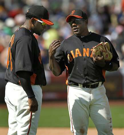 Pablo Sandoval and Miguel Tejada talk about defensive strategy during a spring training game against the Milwaukee Brewers at Scottsdale Stadium in Scottsdale, Ariz., on Monday. Photo: Paul Chinn, The Chronicle