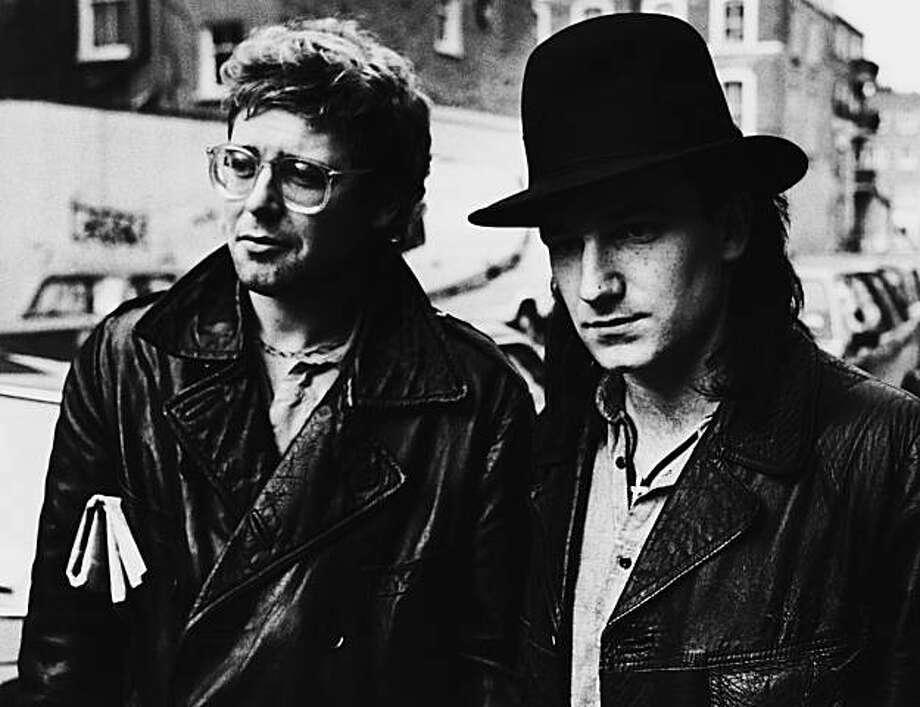U2 bassist Adam Clayton and singer Bono walking down a street, 1985..