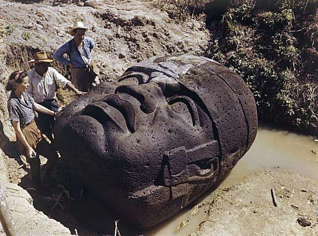 Archeologists study a monumental stone head lying in a ditch. Photo: Richard Hewitt Stewart, National Geographic Stock