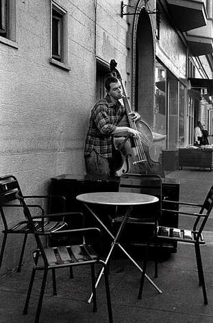 A musician has a smoke and a song in the Mission district. Photo: Russell Yip, The Chronicle