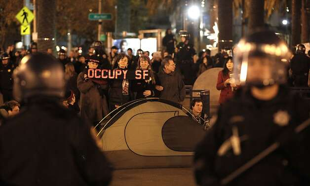 San Francisco police officers surround a group of protesters who are occupying the former encampment, as the Occupy SF group rallies at Justin Herman Plaza in San Francisco, Ca., on Wednesday December 7, 2011. Photo: Michael Macor, The Chronicle