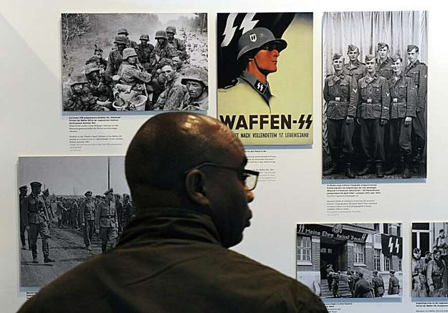 "A visitor looks at photographs of SS troops and propaganda at the new ""Topographie des Terrors"" (Topography of Terror) museum during a press preview in Berlin May 6, 2010. The new museum, which will be inaugurated May 6, 2010, is built on the site of theformer headquarters of both the feared Gestapo and Hitler's elite SS force. While little remains of the original buildings, the new development aims to explain how the Nazi power apparatus worked with ruthless efficiency. Photo: John Macdougall, AFP/Getty Images"