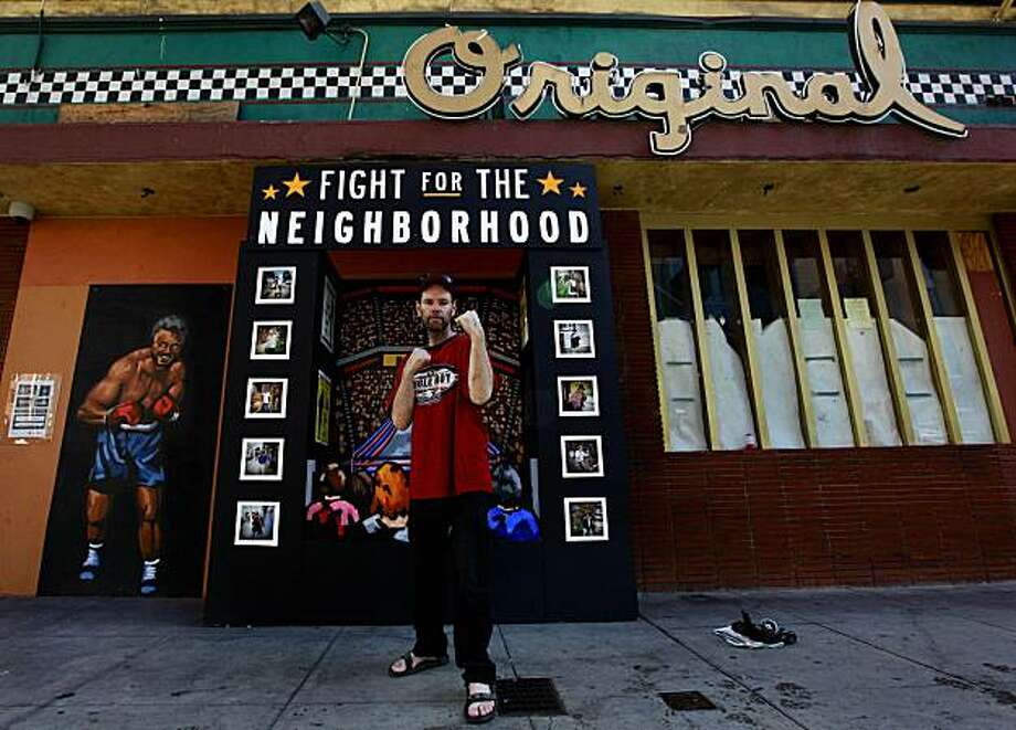 "Michael Papasedero who lives in the Tenderloin, poses in front of the art piece by Chris Treggiari and Billy Mitchell, ""Fight for Your Neighorhood"". The work is part of the ""Art in Storefronts"" project, sponsored by the San Francisco Arts Commission. Photo: Michael Macor, The Chronicle"