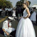 """BULLFIGHTSK-C-20OCT02-LV-CG --- Side Maid, Sandra Medeiros, right, taps her boyfriend, Tony Martinho on the head with her sceptre as celebrants gather in the street of Thornton Ca., on Sunday, October 20, 2002, celebrating the """"Lady of Fatima,"""" Festa. The three-day festival includes a """"Queens' Parade,"""" where over 80 groups representing different Central Valley communities gather for the parade with up to 9 queens per community. The Portugese community of the California Central Valley has kept the tradition of the Bullfights alive as part of the Portugese Festa religious festivals.  Matadors from all over the world participate in the bullfights that range from as far as Fresno to Sacramento.   (PHOTO BY CARLOS AVILA GONZALEZ/THE SAN FRANCISCO CHRONICLE)   CAT    NORTHERN CALIF. MANDATORY CREDIT:  PHOTOG AND SAN FRANCISCO CHRONICLE. MAGS OUT, NO SALES"""