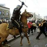 PROTEST46-C-16FEB03-MT-CG A mounted San Francisco Police Officer swings his baton at a crowd of protesters that had gathered after the anti-war march and rally. The crowd was surrounded by police at the corner of 8th street and Market. (Photo by Carlos Avila Gonzalez/The San Francisco Chronicle)    CAT