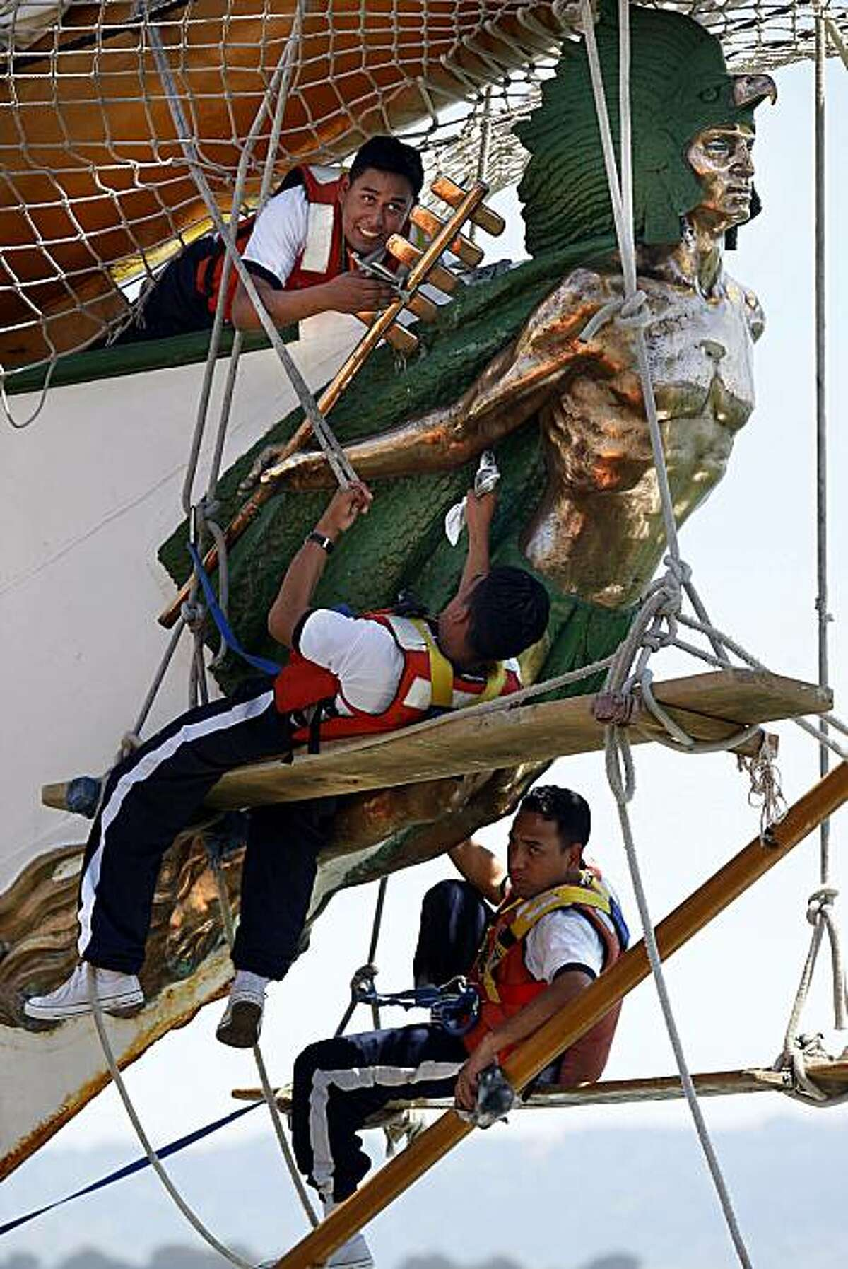 Crew members shine the gold leaf on the figurehead of the last Aztec emperor aboard the Mexican Naval Academy's training vessel,