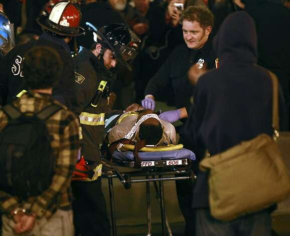 San Francisco Firemen treat an injured Occupy San Francisco man who got in a confrontation with police after approximately 100 protesters reoccupied their former camp, at Justin Herman Plaza in San Francisco, Ca Wednesday December 7, 2011 Photo: Lance Iversen, The Chronicle