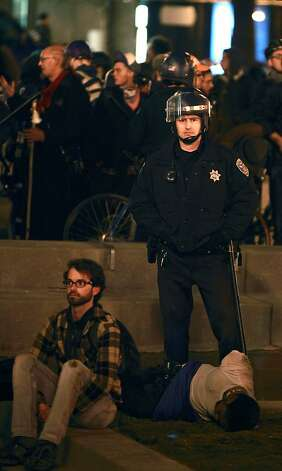 San Francisco police officer stands guard over two men detained after the police surround approximately 100 protesters who are occupying their former camp, at Justin Herman Plaza in San Francisco, Ca Wednesday December 7, 2011 Photo: Lance Iversen, The Chronicle