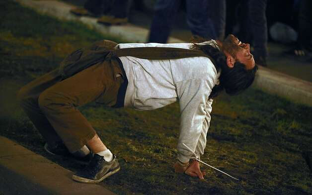 A occupy San Francisco man stretches during his detainment after police officers surround approximately 100 protesters who were occupying their former camp, at Justin Herman Plaza in San Francisco, Ca Wednesday December 7, 2011 Photo: Lance Iversen, The Chronicle