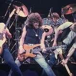 Circa 1980: Pop group Status Quo performing..