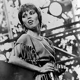 American rock and pop singer Pat Benatar glances over her shoulder as she plays air guitar on stage, early 1980s. She is dressed in a sweatshirt, cut so that it has fringes. One of her bandmates is visible in the background..