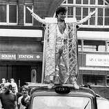 25th May 1984: Glam rock star Gary Glitter pulls a crowd in London's Leicester Square, standing on the roof of a black cab dressed in one of his eye-catching silver costumes as it drives through the streets..