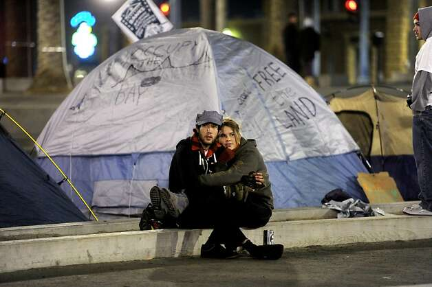 Occupy SF protesters sit by one of four tents erected in Justin Herman Plaza on Wednesday, Dec. 7, 2011, in San Francisco. Photo: Noah Berger, Special To The Chronicle