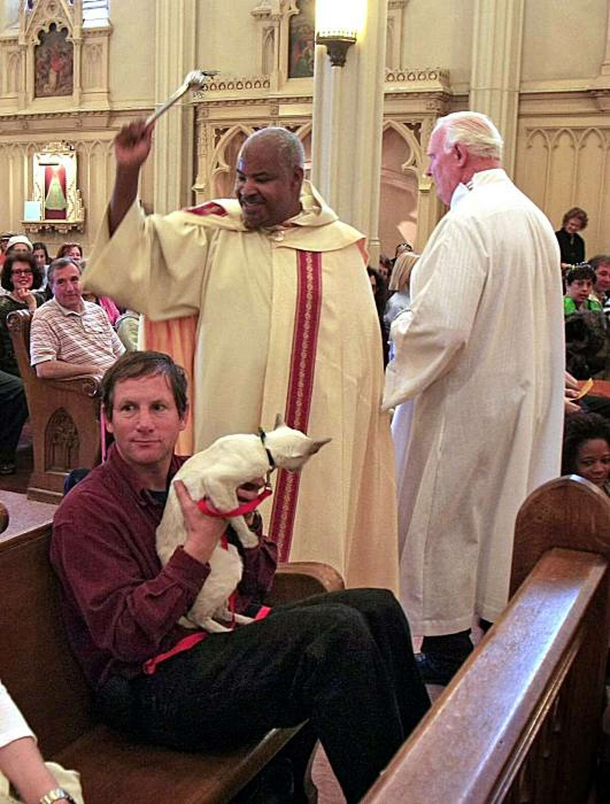 Tom Ross and his cat, Kyro, received a blessing from Deacon Charles McNeil at Saturday's North Beach annual street festival, which includes animal blessings at The St. Francis Church.