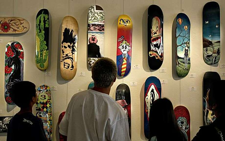 Visitors to the gallery check out the array of designs. The skateboard has become the canvas for artists to display their works, over 170 pieces of art, on Tuesday Apr. 6, 2010, are on view at Gallery 28 in the North Beach neighborhood of San Francisco, Calif. Photo: Michael Macor, The Chronicle