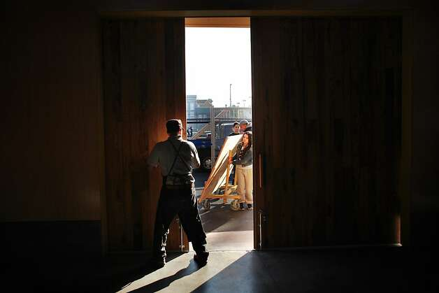 Gus Amador (left), carpentry teacher, slides open the doors of a new industrial arts building allowing advanced carpentry students to wheel in plywood on a dolly as they work together to rough frame a stage being built in the new industrial arts building at John O'Connell High School on  Wednesday, December 7, 2011 in San Francisco, Calif.  The stage was being built for a ceremony for the new building to be held the next day. Photo: Lea Suzuki, The Chronicle
