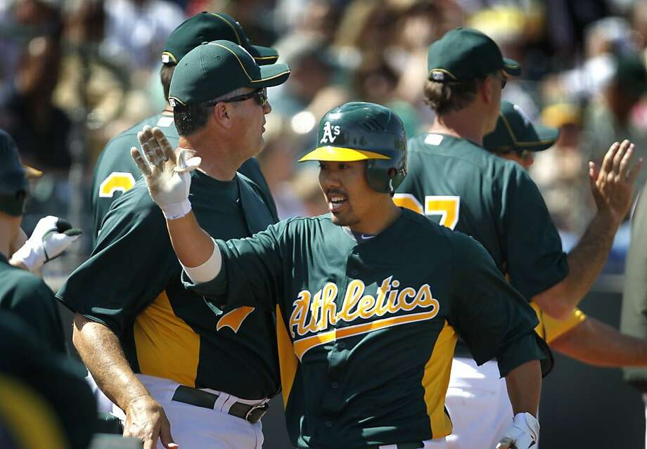 Kurt Suzuki is welcomed back to the dugout after his two-run blast in the 2nd inning of the Oakland A's 6-5 win over the Chicago Cubs in a spring training baseball game at Phoenix Municipal Stadium in Phoenix, Ariz. on Thursday, March 17, 2011. Photo: Paul Chinn, The Chronicle