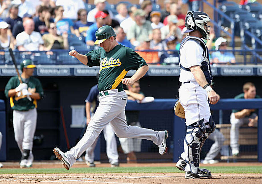 PEORIA, AZ - MARCH 06:  Cliff Pennington #2 of the Oakland Athletics scores a run past catcher Gregg Zaun #27 of the San Diego Padres during the first inning of the spring training game at Peoria Stadium on March 6, 2011 in Peoria, Arizona. Photo: Christian Petersen, Getty Images